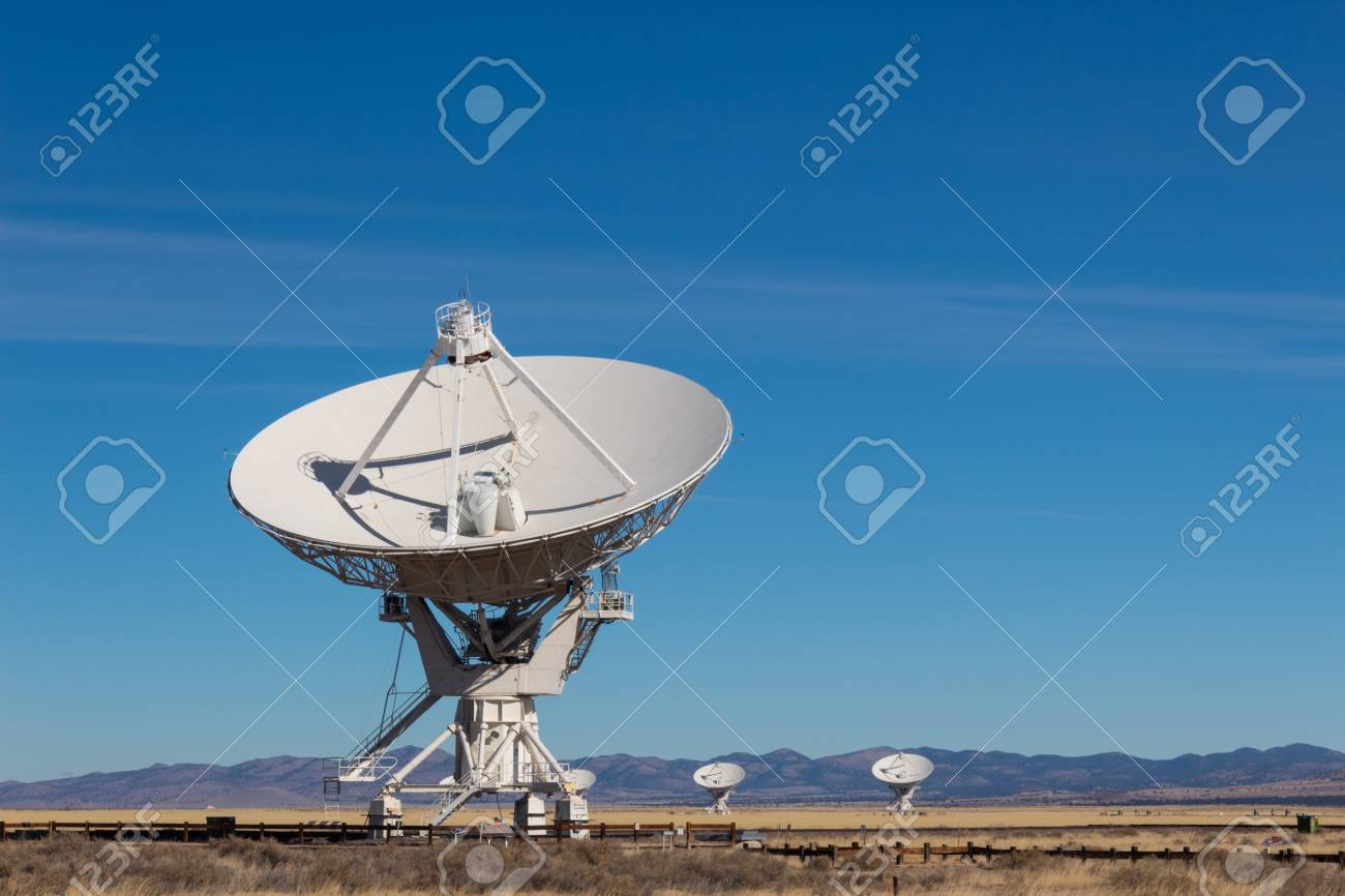 Very Large Array radio antenna dish close with others in distance, blue sky copy space, horizontal aspect - 117554519