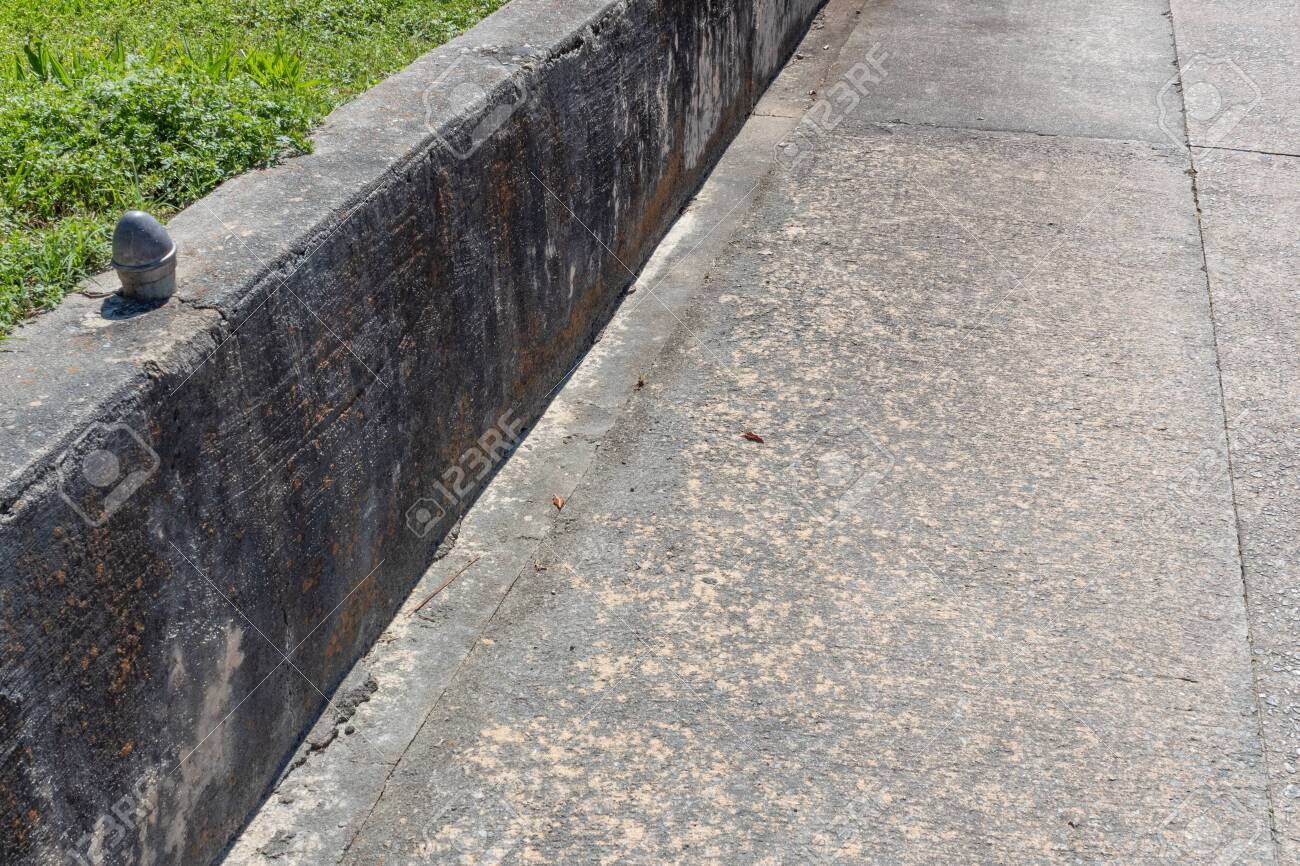 Gray Concrete Retaining Wall Along A Driveway With Grass And