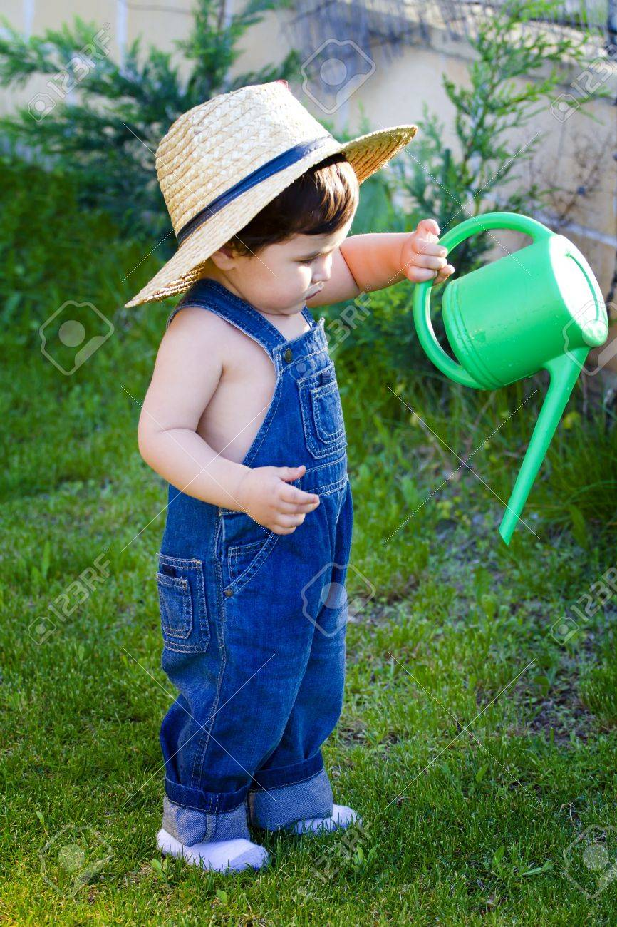 little baby gardener with hat watering the plants Stock Photo - 10316497 0f48ccb75c6b