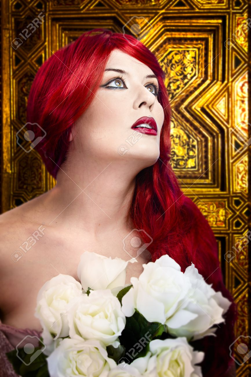 Gothic woman, faith concept. Red hair beautiful girl over  medieval gold background Stock Photo - 13130684