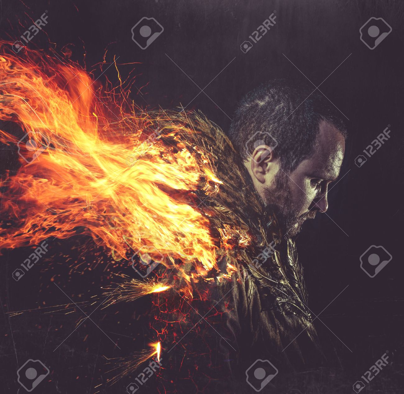 fallen angel, jacket man with golden feathers on the wings and fire Stock Photo - 30572999