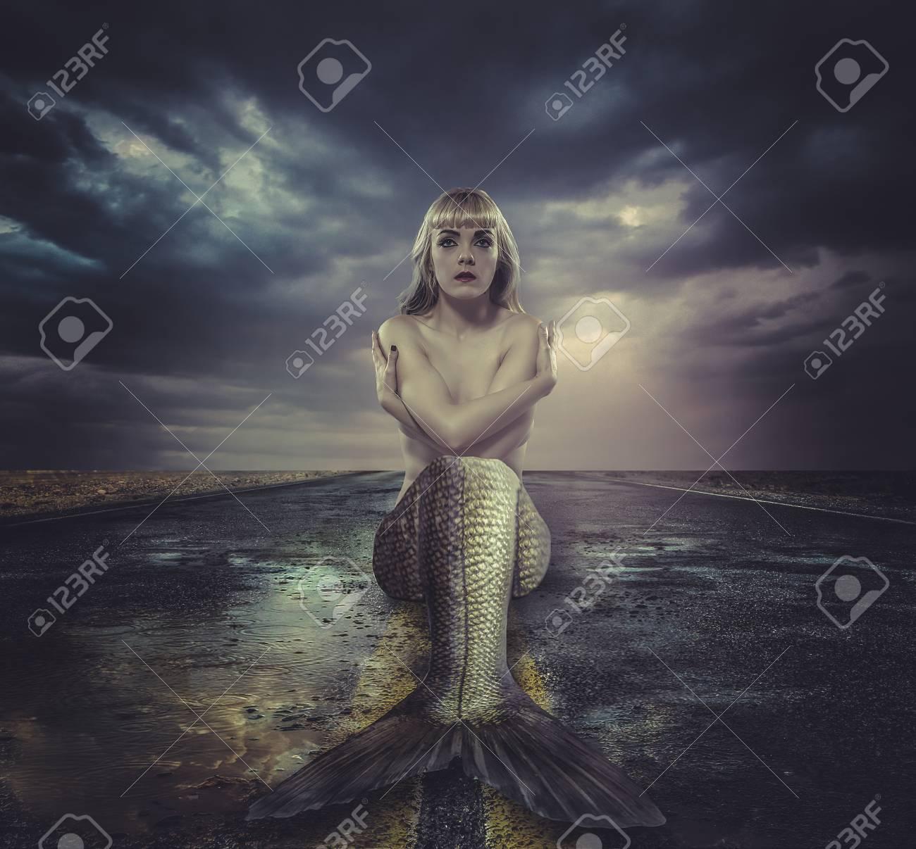 mermaid sitting on a deserted road - 30352654