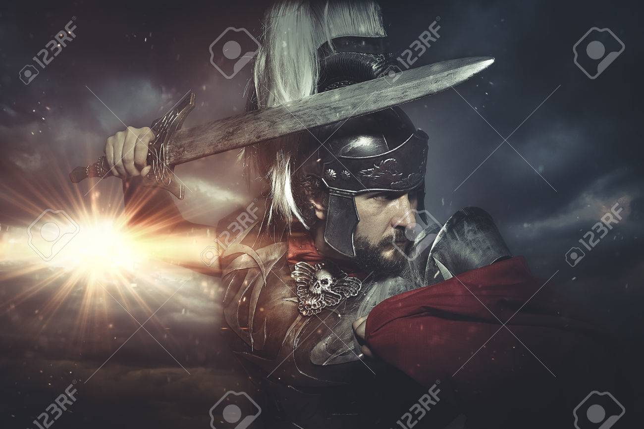 Legionary warrior helmet, armor and red cape on a battlefield, conflict and struggle in the Roman Empire - 57235029
