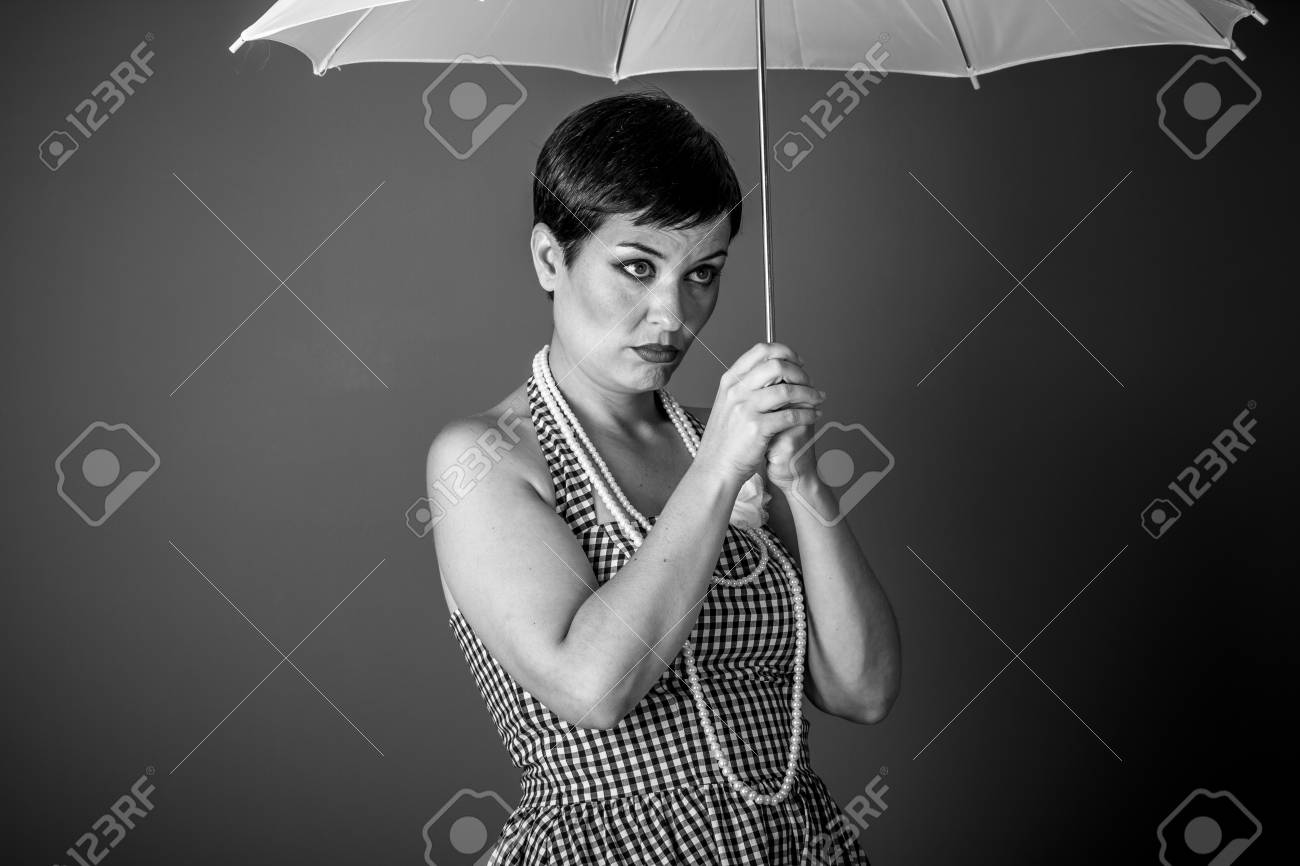Cheerful girl vintage 50s dress with white umbrella over blue background stock photo 86319505