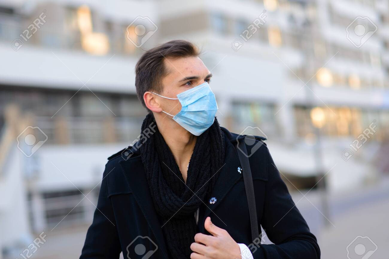 Portrait of young handsome businessman with face mask in quarantine of flu. Photo in caffee with laptop, mobile phone. Coronavirus pandemic. - 150046982