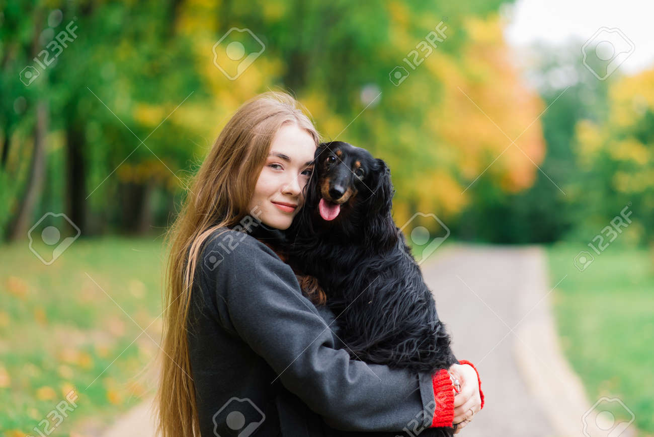 Young attractive woman holding her dachshund dog in her arms outdoors in sunrise in park at autumn time - 167067152