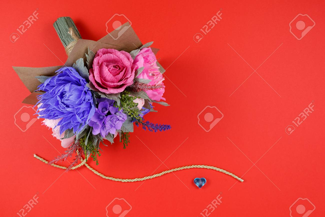 A Bouquet Of Colorful Paper Flowers And A Small Blue Heart On