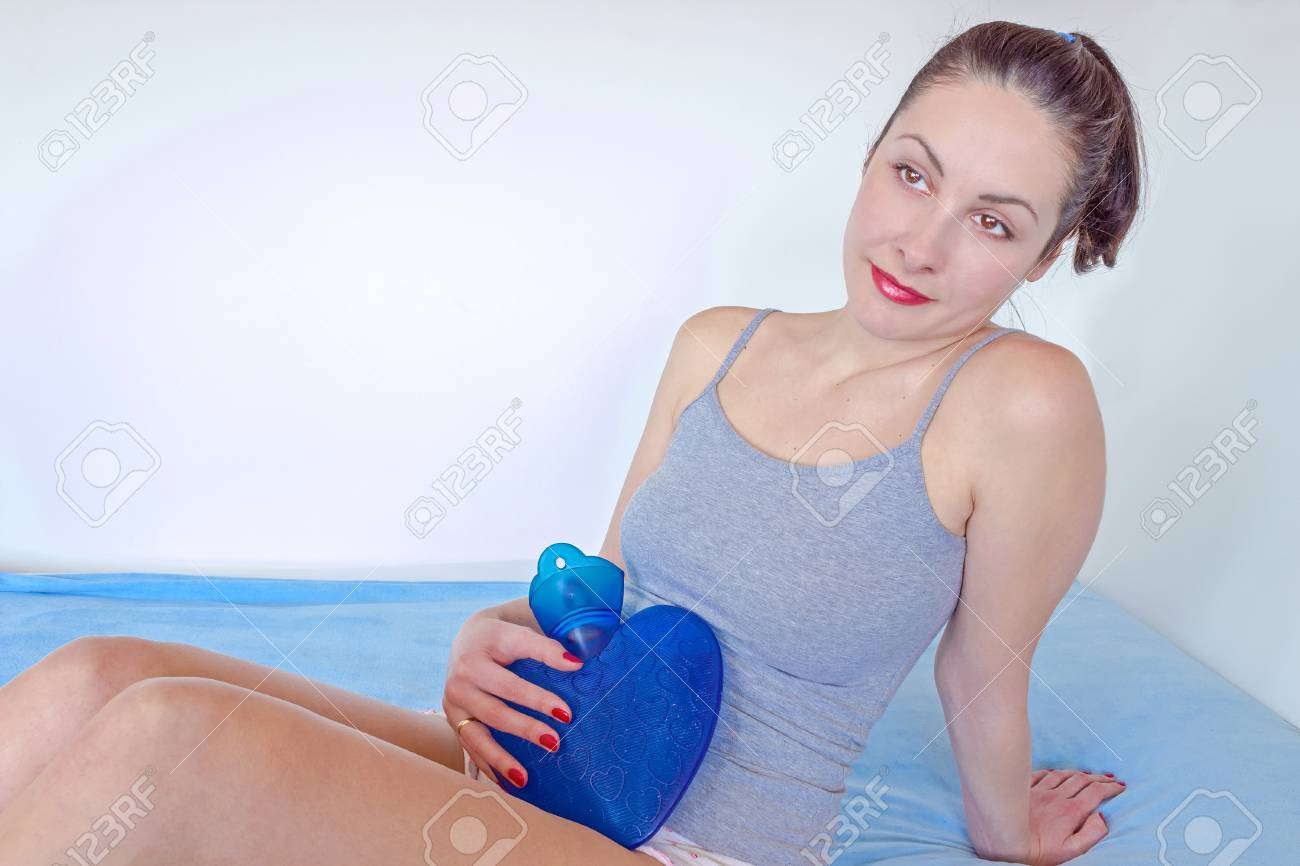 A young woman holding a water bottle on her stomach to alleviate stomach problems, photography Stock Photo - 18342991