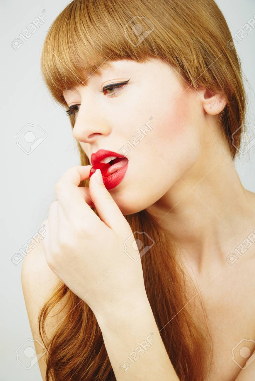 beautiful red hair woman eating a red candy Stock Photo - 9424925