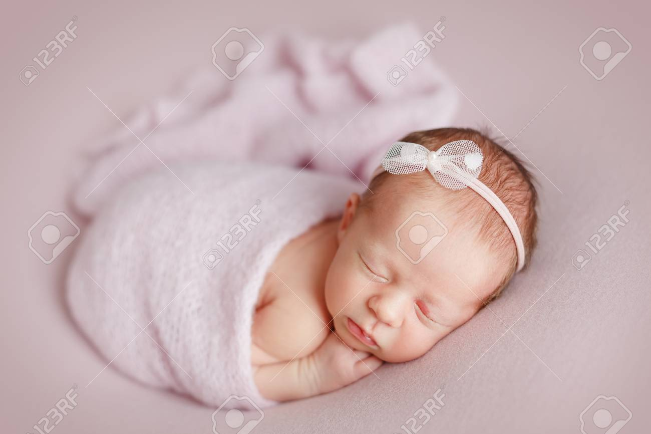 Cute Newborn Baby Girl With A Bow On Her Head Sleeping On A Pink Stock Photo Picture And Royalty Free Image Image 102128123