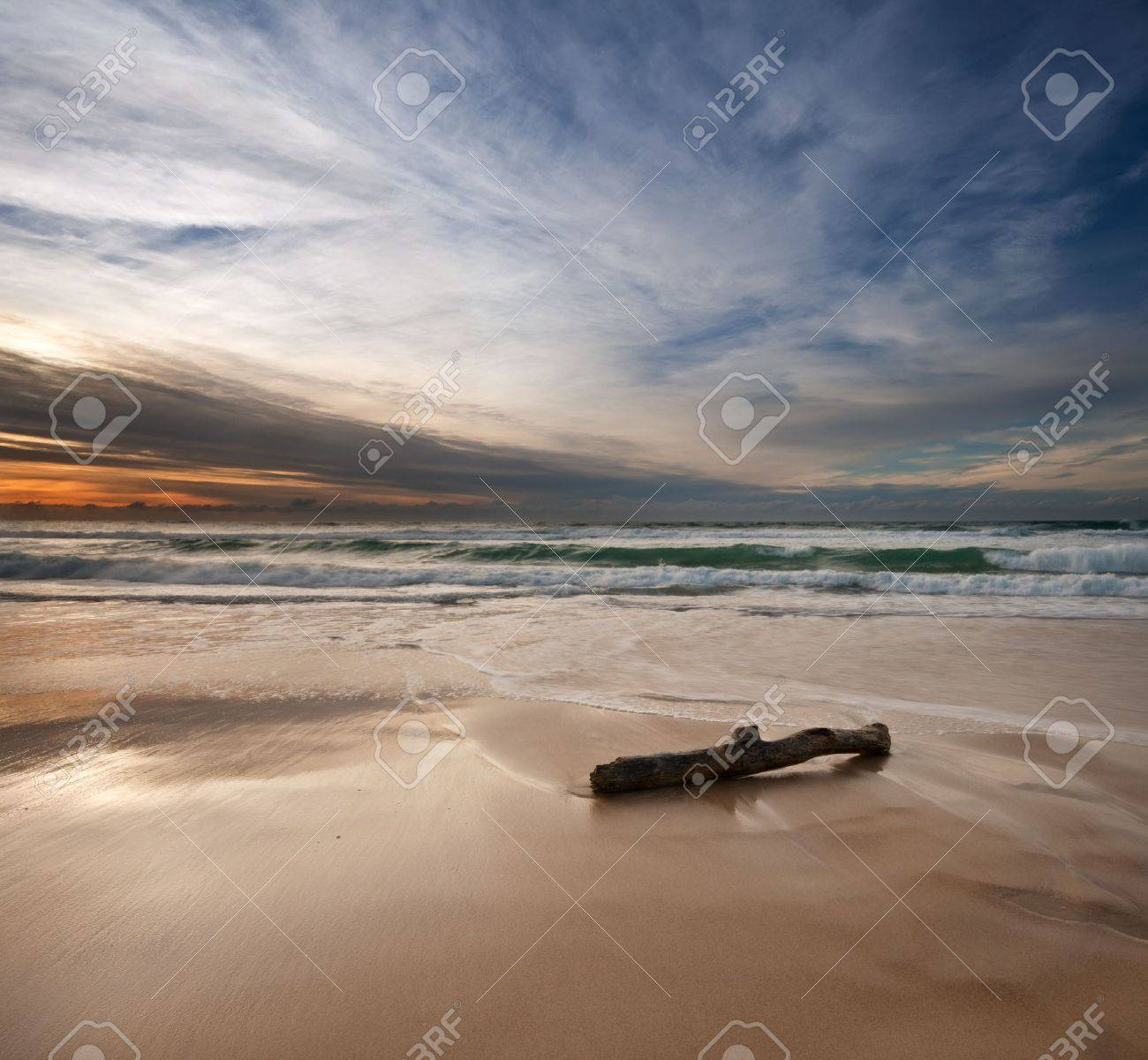 sunrise on beach with log in foreground on square format Stock Photo - 8490394