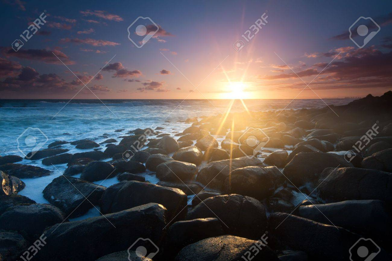 sunrise with interesting full of rocks foreground and nice clouds color in background Stock Photo - 8490390