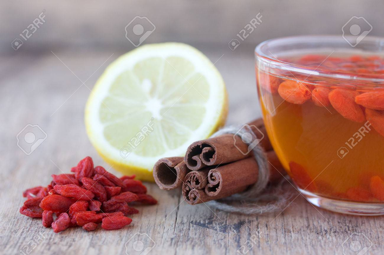 Cup Of Delicious Dietary Goji Berry Tea On Wooden Desk With Lime