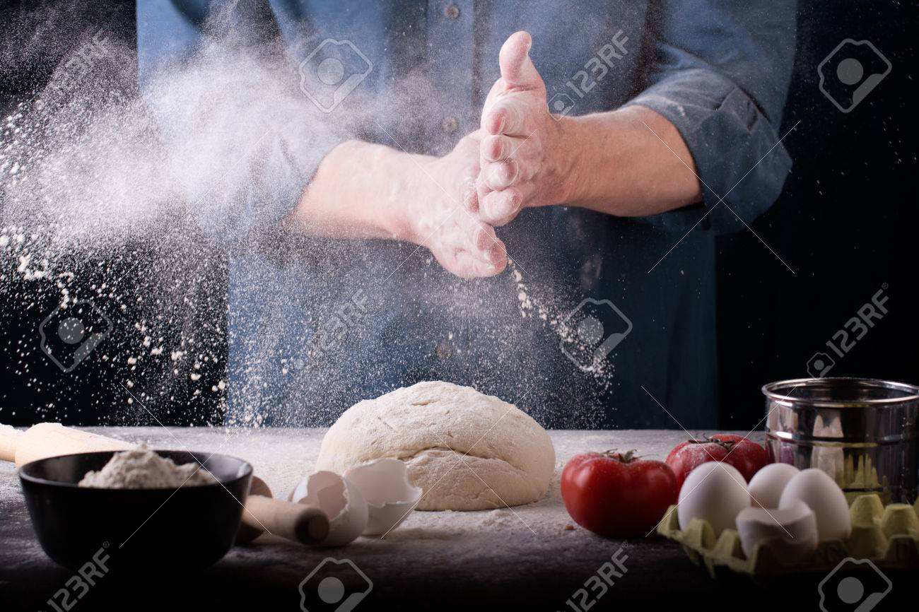 Baker prepares the dough on table, male hands knead the dough with flour, homemade dough for bread or pizza, top view, rustic style - 58672967