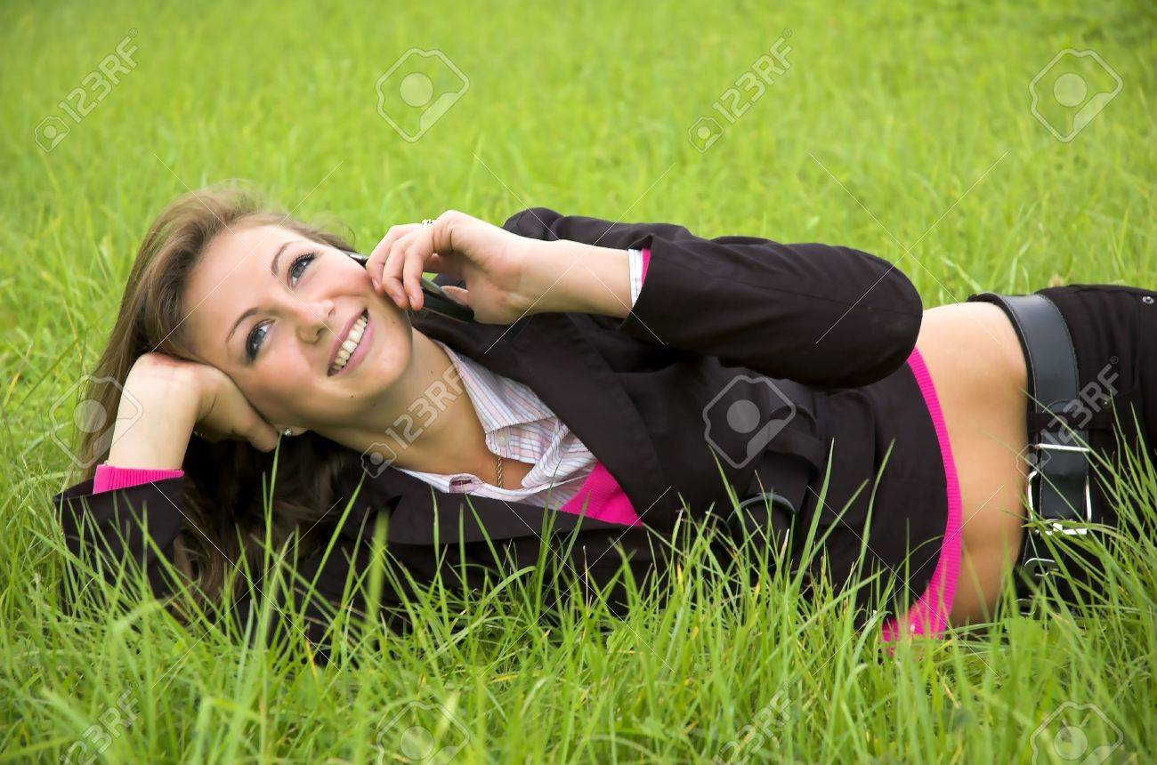 The girl speaks by phone laying on a green grass Stock Photo - 1807748