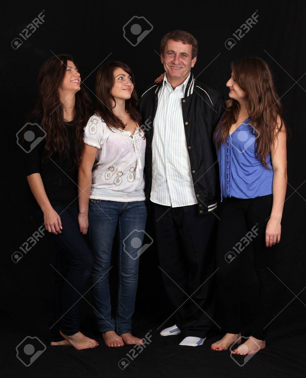 three happy sisters and dad against black background Stock Photo - 7927313