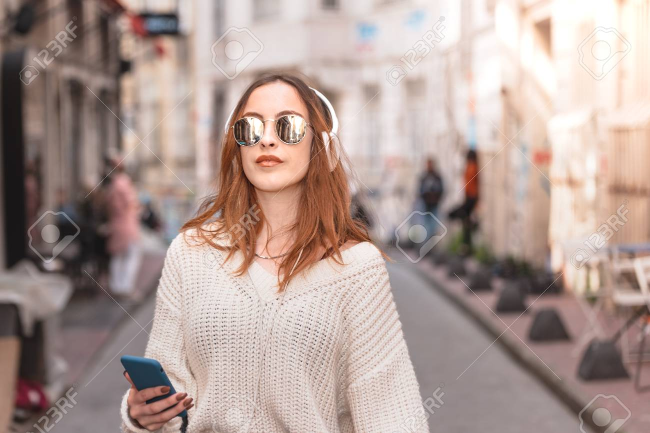 Beautiful attractive young trendy girl in jumper and jeans with headphones smartphone and sunglasses listen music while walking in crowd - 122219190