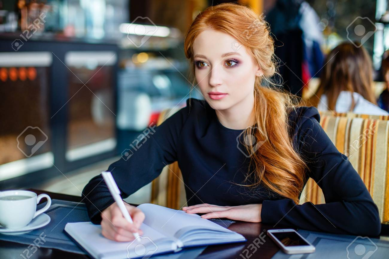 Young creative female writer pondering over conclusion of essay to give the reader something to think about inspiring by warm atmosphere in comfortable coffee shop writing down script into notebook - 88302450