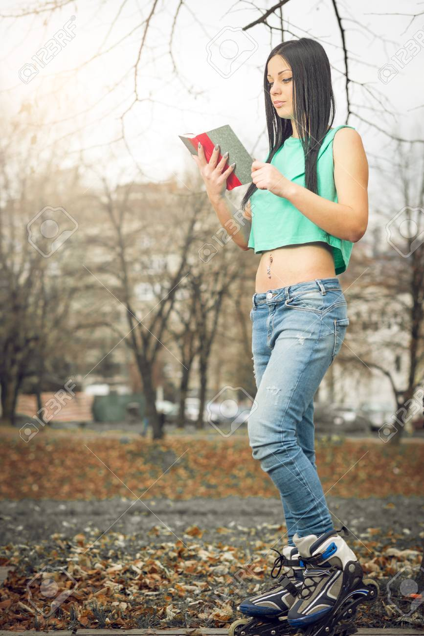 Roller skates book - Stock Photo Young Adult Girl Reading A Book On Roller Skates In Park Outdoor