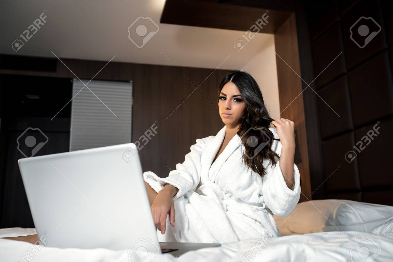 Chambre De Jeune Adulte ordinateur portable dans le lit de la chambre d'hôtel. jeune adulte jolie  femme attirante en utilisant un ordinateur portable en position couchée sur