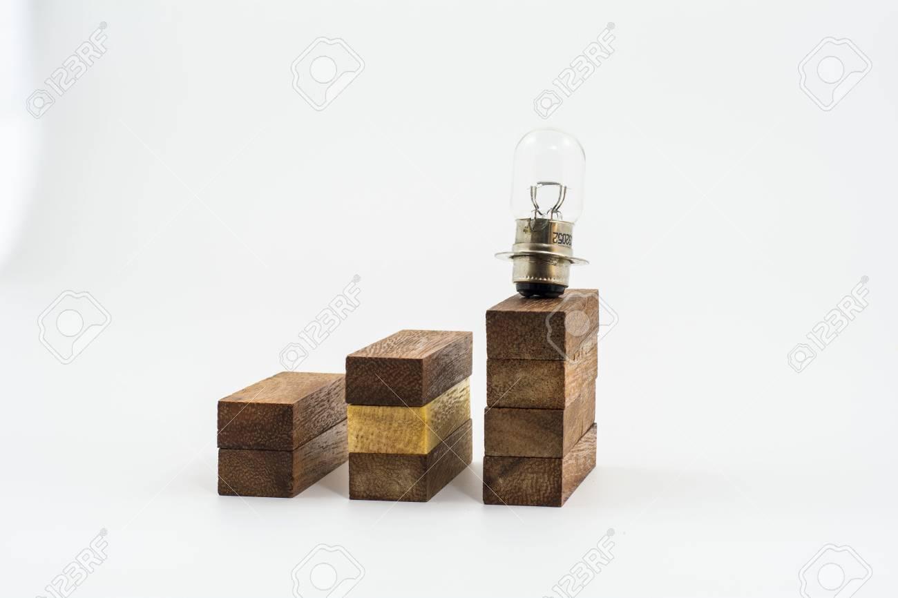 Lampada sulle statistiche Business Graph colonne di legno isolato su bianco