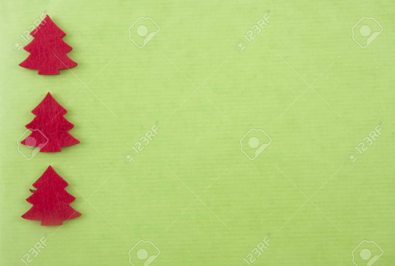Christmas background with three red felt christmas trees on bright green paper Stock Photo - 8292365