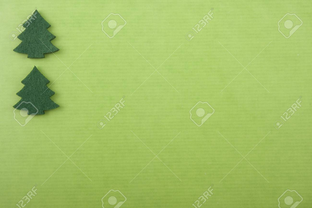 Christmas background with two felt green christmas trees on bright green paper Stock Photo - 8292367