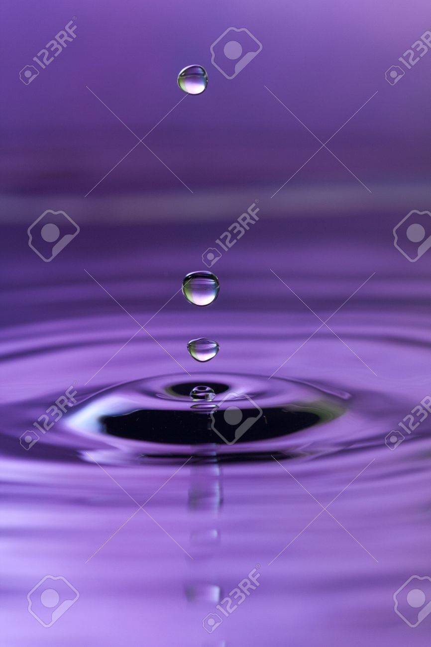 A purple abstract background of a close up of transparent water drops falling in water, making beautifull ripples and flowing waves in the surface and showing the pure energy it creates. Small depth of field. Stock Photo - 8970703