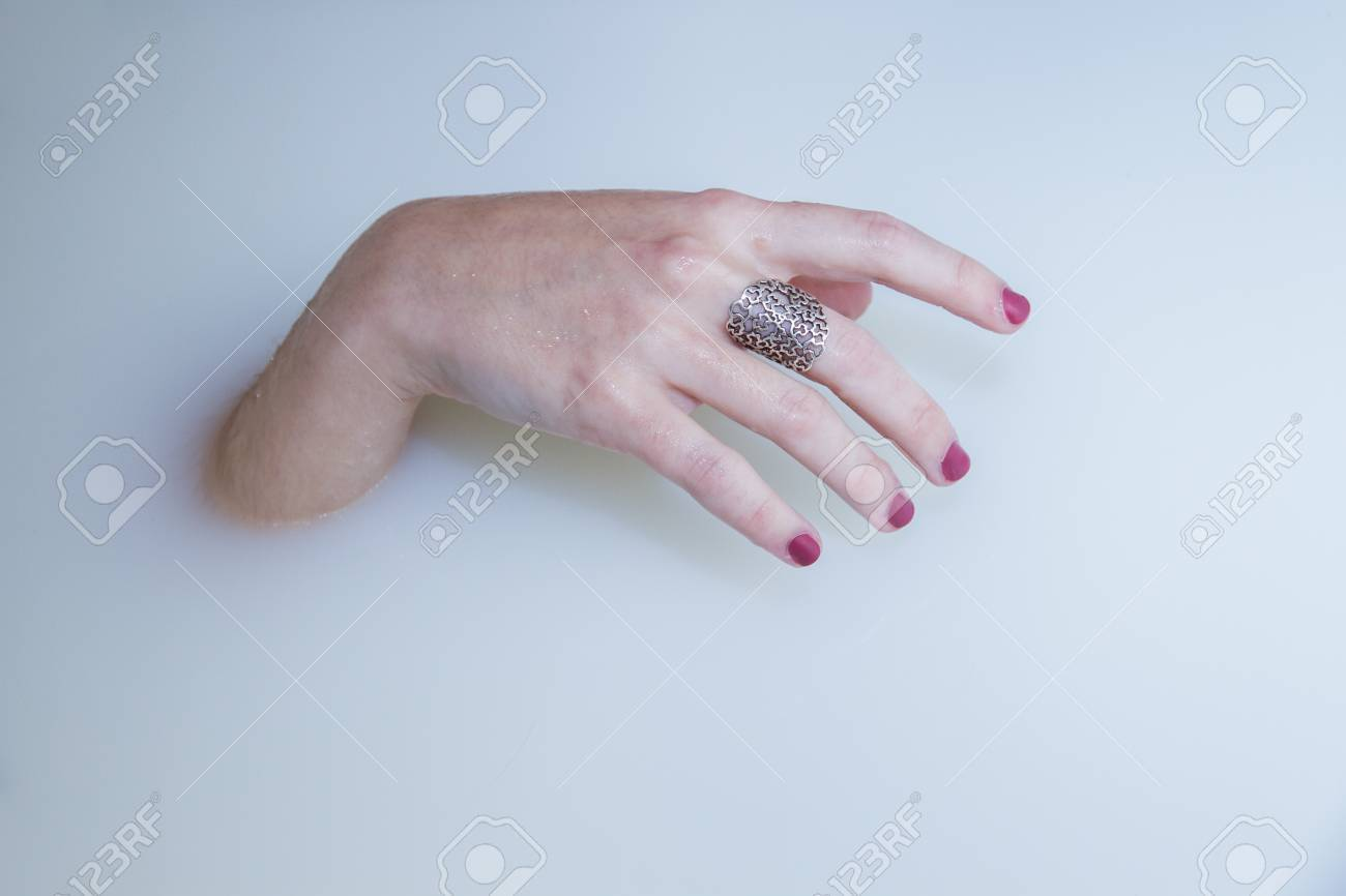 A Girl\'s Hand Protruding From A Bath Of Water And Milk In A Bathtub ...