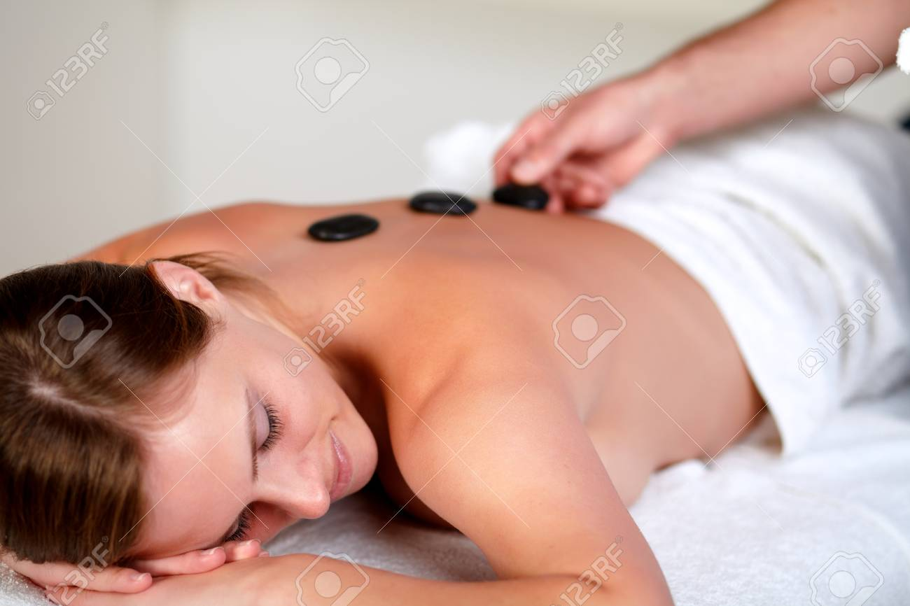 Close up portrait of a tired young woman relaxing at a spa and receiving a hot stone massage Stock Photo - 14247750