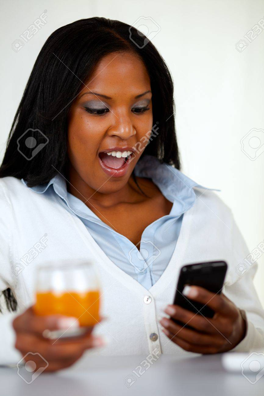 Portrait of a surprised young woman reading a message on mobile at soft composition Stock Photo - 14463726