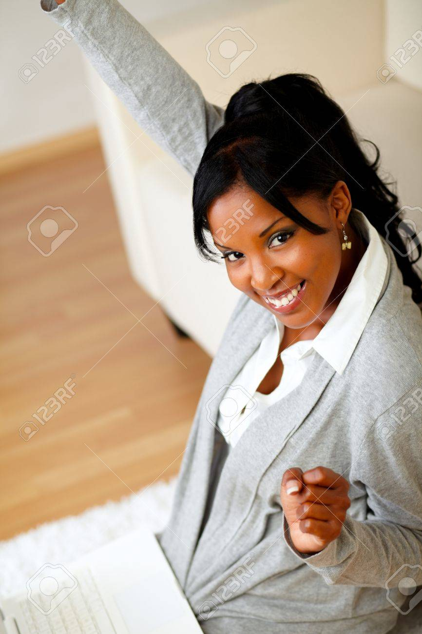 Top view portrait of a happy young woman sitting at home on the floor in front her laptop while is celebrating a victory and looking to you Stock Photo - 14641202