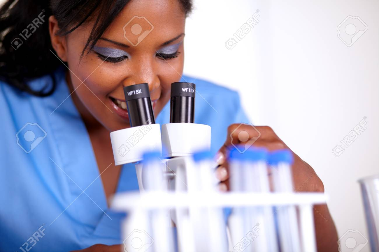 Charming medical doctor woman using a microscope at hospital Stock Photo - 15100271