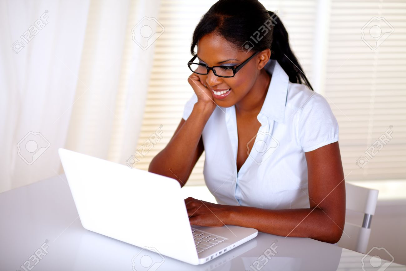 Charming secretary browsing the internet on laptop at workplace with black glasses - copyspace Stock Photo - 15154864