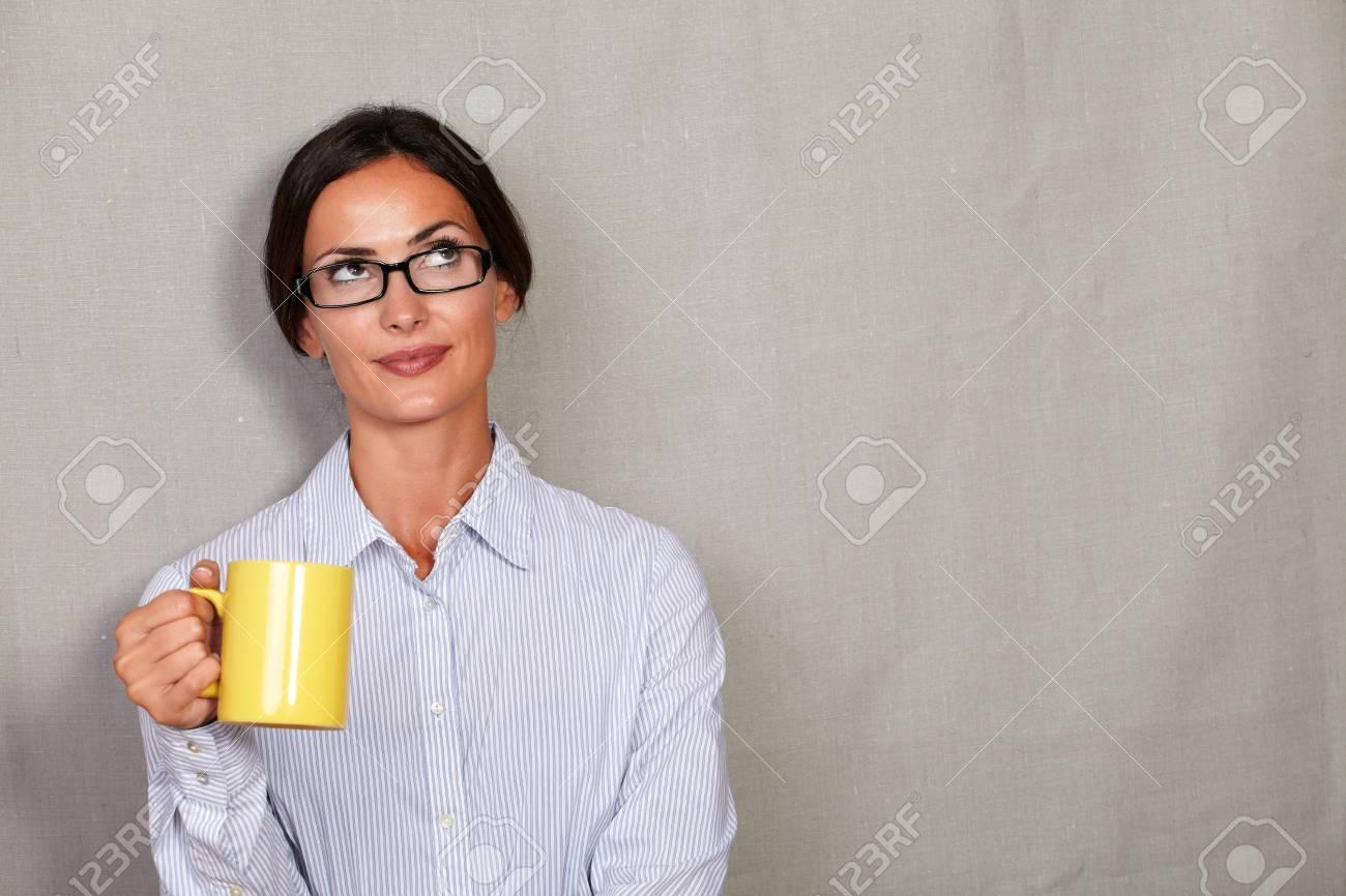 d4ff7691cb Foto de archivo - Señora adulta pensativa sosteniendo la taza de café en  botón de camisa y gafas mientras mira lejos reflexiva sobre fondo gris de  la ...