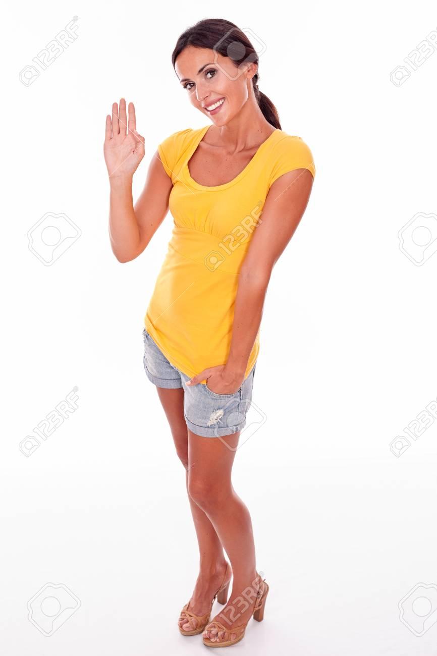 6af0ac6f16a0 Mujer morena agitando mientras mira a la cámara y que llevaba una camiseta  amarilla y pantalones vaqueros cortos aislados sonriendo