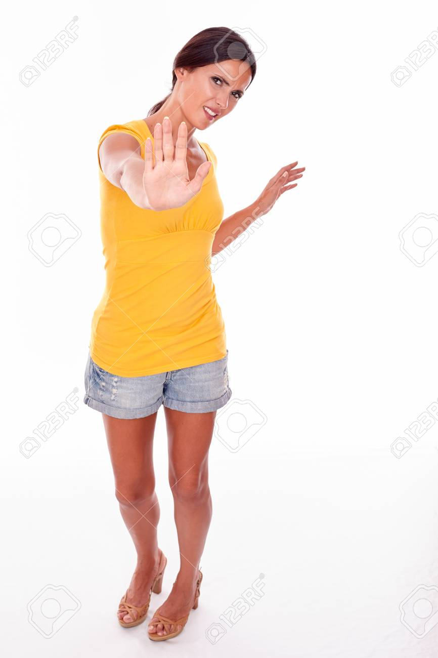 Frowning brunette woman gesturing to stop with her left hand