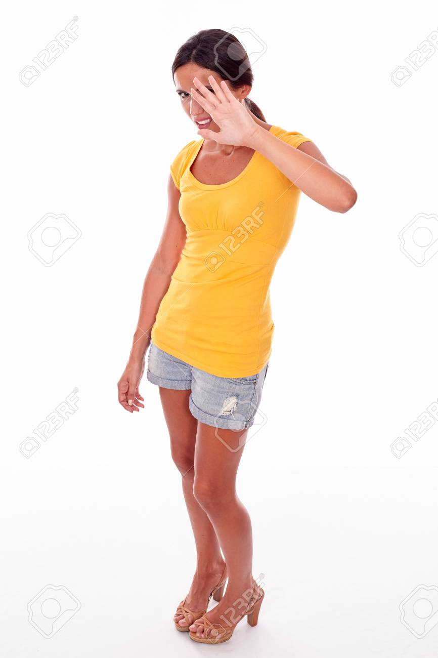 Frowning brunette woman gesturing stop with her left hand obscuring