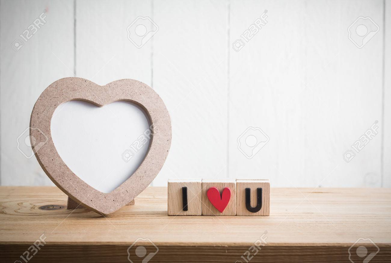 Heart Shaped Photo Frame With I Love U In Cube On Wood Table Stock