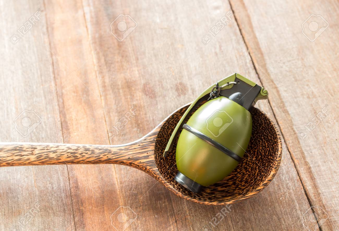 Hand grenade M26A1 model in spoon on wood background