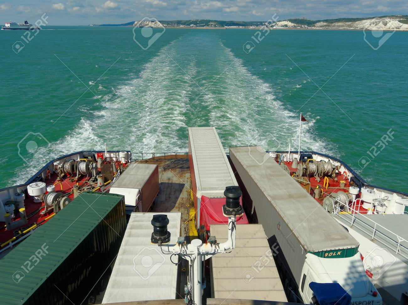 Trucks on ferry floats by English Channel on a sunny day