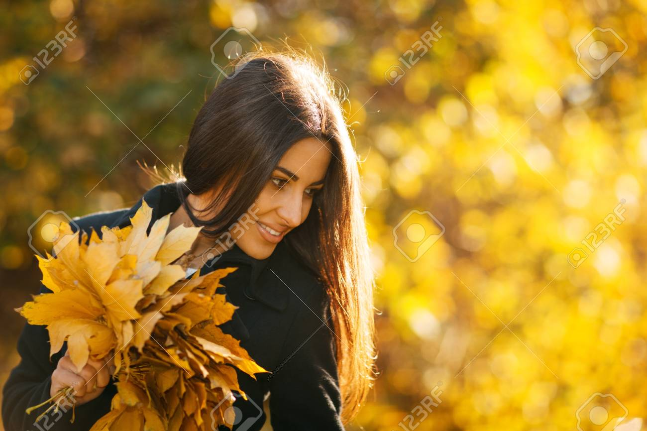 Autumn portrait of young woman in fall colors outdoors holding a bunch of yellow maple leaves Stock Photo - 16159305