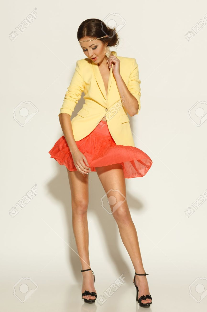 Full Length Of Fashion Model Posing In Mini Skirt Fluttering Stock