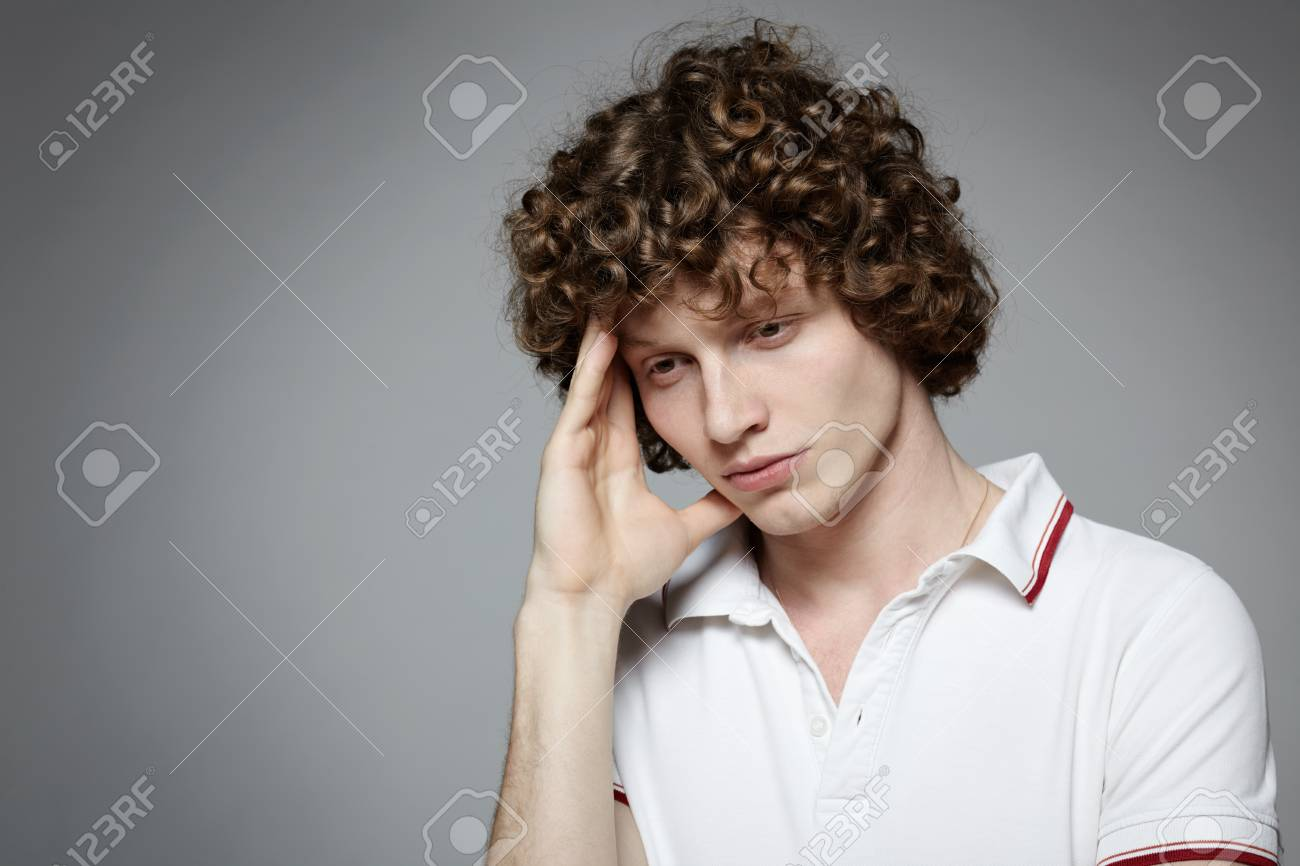 Portrait of young man with headache holding forehead in pain over gray background Stock Photo - 16796509