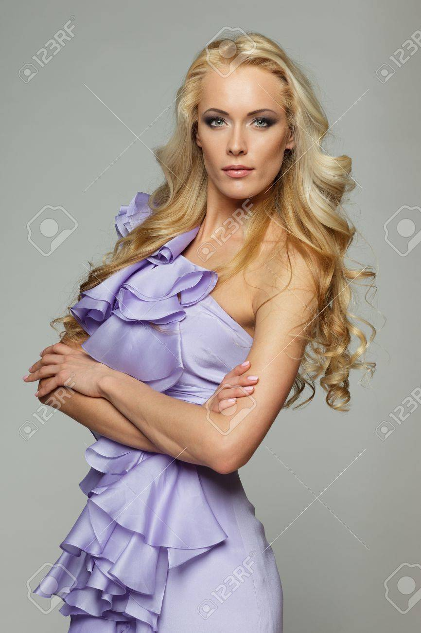 Beautiful female with long blond hair standing with folded hands, over gray background Stock Photo - 17055103