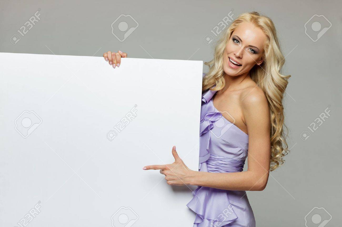 Woman pointing at a blank board over gray background Stock Photo - 17055114