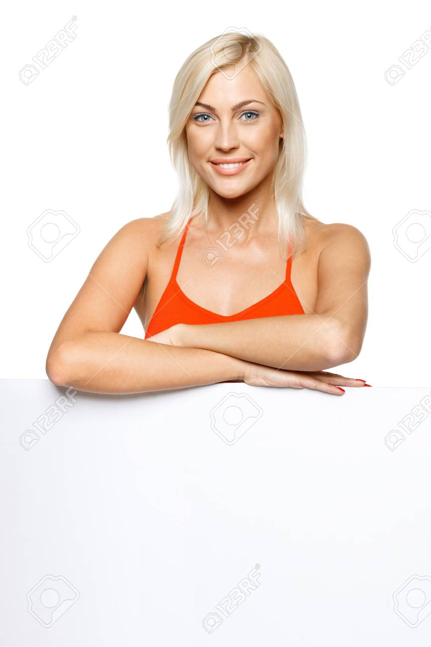 Smiling woman standing behind and leaning on a white blank billboard   placard, over white background Stock Photo - 17537496