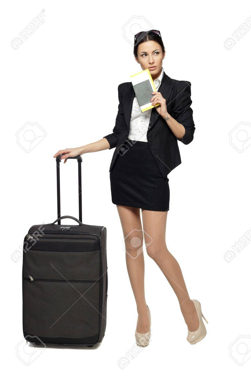 Full length portrait of young business woman standing with her travel bag, holding the tickets with passport, looking sideways at blank copy space, isolated on white background Stock Photo - 18303446