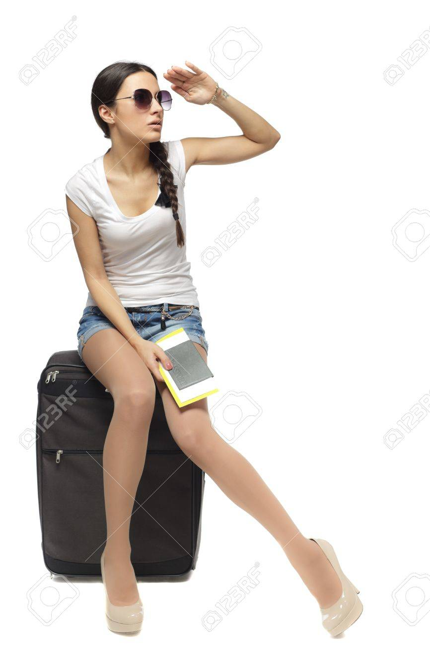 Full length of young woman sitting on her travel bag and holding the tickets with passport looking faraway isolated on white background Stock Photo - 18303437