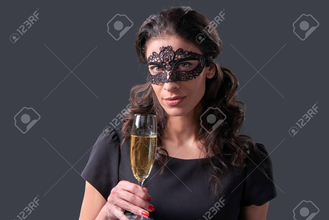 f12b15548a7 Foto de archivo - Mujer sensual vestido de negro de la mascarada máscara de  carnaval en la fiesta de celebración de un vaso con champán.